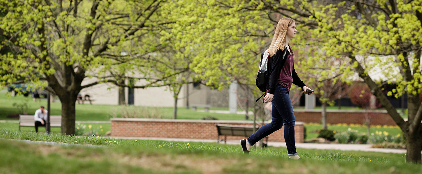 Student walking through campus in Spring