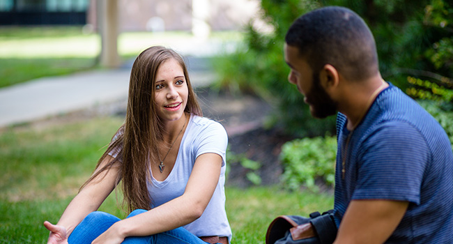 Students talking on campus lawn